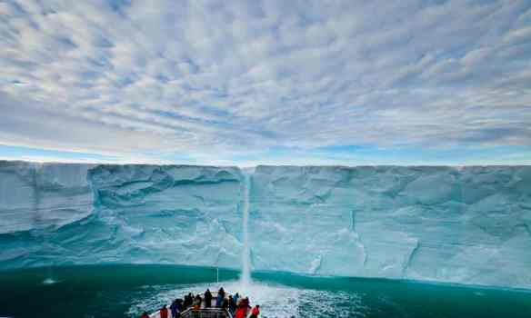 Under a blanket of clouds, tourists watch a meltwater waterfall on an icecap. Photograph: Ralph Lee Hopkins/National Geographic Society/Corbis